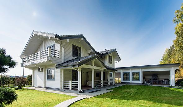 Светлые стены деревянного дома в сочетании с темной крышей